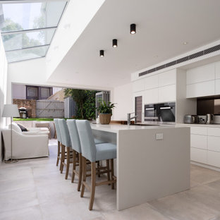 This is an example of a contemporary l-shaped kitchen in Sydney with flat-panel cabinets, white cabinets, stainless steel appliances, with island, grey floor and grey benchtop.