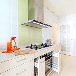 Diseño de cocina comedor de galera, moderna, pequeña, sin isla, con fregadero bajoencimera, armarios con paneles lisos, puertas de armario amarillas y electrodomésticos de acero inoxidable