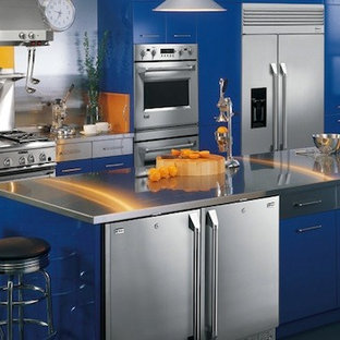 Large industrial enclosed kitchen photos - Inspiration for a large industrial single-wall concrete floor enclosed kitchen remodel in San Diego with an undermount sink, flat-panel cabinets, blue cabinets, stainless steel countertops, metallic backsplash, metal backsplash, stainless steel appliances and an island
