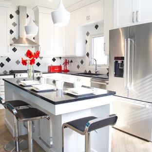 トロントの中サイズのエクレクティックスタイルのおしゃれなキッチン (アンダーカウンターシンク、シェーカースタイル扉のキャビネット、白いキャビネット、クオーツストーンカウンター、黒いキッチンパネル、磁器タイルのキッチンパネル、シルバーの調理設備の、淡色無垢フローリング、ベージュの床、グレーのキッチンカウンター) の写真