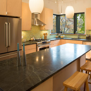 Inspiration for a large contemporary l-shaped eat-in kitchen in New York with medium hardwood floors, with island, a drop-in sink, flat-panel cabinets, light wood cabinets, limestone benchtops, green splashback, glass tile splashback and stainless steel appliances.