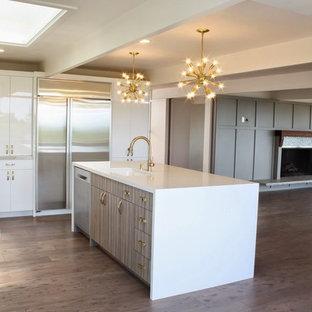 ロサンゼルスの大きいモダンスタイルのおしゃれなキッチン (アンダーカウンターシンク、フラットパネル扉のキャビネット、白いキャビネット、珪岩カウンター、ベージュキッチンパネル、磁器タイルのキッチンパネル、シルバーの調理設備の、クッションフロア、茶色い床) の写真