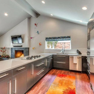 Photo of a mid-sized contemporary l-shaped open plan kitchen in Oklahoma City with an undermount sink, flat-panel cabinets, stainless steel cabinets, terrazzo benchtops, white splashback, porcelain splashback, stainless steel appliances, dark hardwood floors, a peninsula and brown floor.