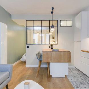 Aménagement d'une cuisine ouverte scandinave avec un évier posé, un placard à porte plane, des portes de placard blanches, un plan de travail en bois, une crédence blanche, une crédence en carrelage métro, une péninsule et un sol multicolore.