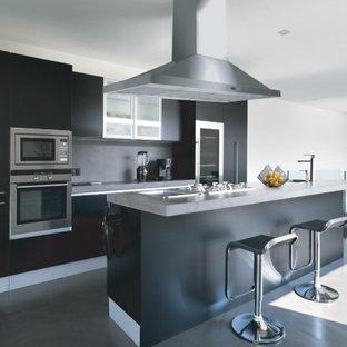 Immagine di una cucina minimal di medie dimensioni con ante lisce, ante nere, top in zinco, paraspruzzi grigio, elettrodomestici in acciaio inossidabile, isola, pavimento grigio e top grigio