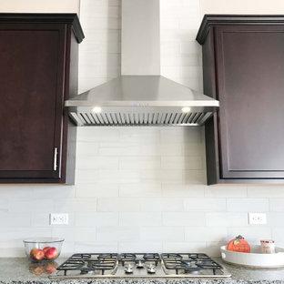 Ejemplo de cocina comedor lineal, minimalista, de tamaño medio, con armarios con paneles empotrados, puertas de armario de madera en tonos medios, encimera de granito, salpicadero blanco, salpicadero de azulejos de terracota, electrodomésticos de acero inoxidable y encimeras grises