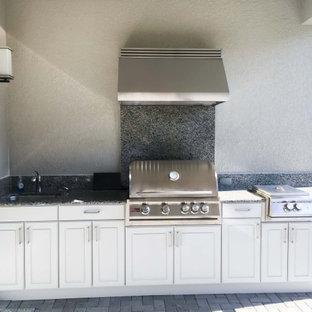 Ejemplo de cocina comedor lineal, minimalista, de tamaño medio, con fregadero de un seno, encimera de granito, salpicadero multicolor, puertas de granito, electrodomésticos de acero inoxidable, suelo de ladrillo, suelo marrón y encimeras marrones