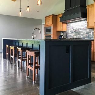 中くらいのモダンスタイルのおしゃれなキッチン (落し込みパネル扉のキャビネット、淡色木目調キャビネット、マルチカラーのキッチンパネル、レンガのキッチンパネル、シルバーの調理設備、セラミックタイルの床、グレーの床、黒いキッチンカウンター、三角天井) の写真