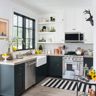 Photo of a mid-sized transitional l-shaped kitchen in Los Angeles with a farmhouse sink, shaker cabinets, green cabinets, white splashback, stainless steel appliances, light hardwood floors, no island, beige floor and porcelain splashback.