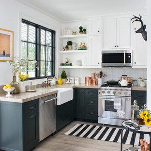 Mittelgroße Klassische Küche ohne Insel in L-Form mit Landhausspüle, Schrankfronten im Shaker-Stil, grünen Schränken, Küchenrückwand in Weiß, Küchengeräten aus Edelstahl, hellem Holzboden, beigem Boden und Rückwand aus Porzellanfliesen in Los Angeles