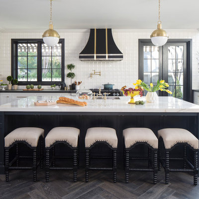 Inspiration for a transitional u-shaped dark wood floor and brown floor eat-in kitchen remodel in Los Angeles with an undermount sink, shaker cabinets, white cabinets, white backsplash, ceramic backsplash, stainless steel appliances and an island