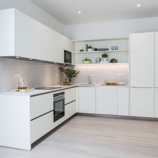 This is an example of a medium sized contemporary l-shaped kitchen/diner in London with an integrated sink, flat-panel cabinets, white cabinets, composite countertops, white splashback, stone slab splashback, black appliances, laminate floors, no island, brown floors and white worktops.