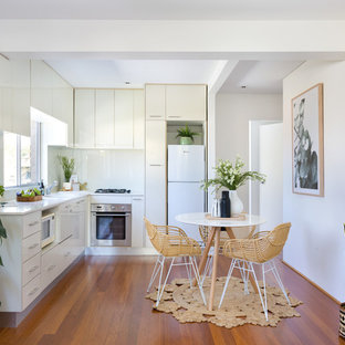 Photo of a contemporary l-shaped eat-in kitchen in Sydney with an undermount sink, flat-panel cabinets, white cabinets, white splashback, white appliances, medium hardwood floors, no island, brown floor and white benchtop.