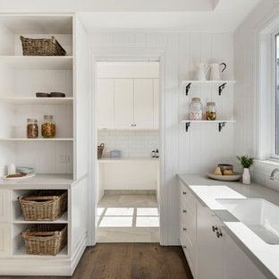 Beach style l-shaped kitchen in Melbourne with an undermount sink, shaker cabinets, white cabinets, white splashback, medium hardwood floors, brown floor and grey benchtop.