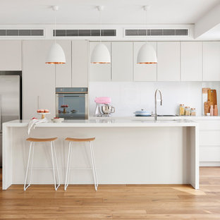 Design ideas for a contemporary single-wall open plan kitchen in Melbourne with an undermount sink, flat-panel cabinets, beige cabinets, white splashback, stainless steel appliances, light hardwood floors, with island, beige floor, quartz benchtops and glass sheet splashback.