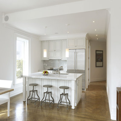 Example of a small trendy galley medium tone wood floor and brown floor eat-in kitchen design in New York with stainless steel appliances, an undermount sink, recessed-panel cabinets, white cabinets, quartzite countertops, stone slab backsplash, an island and gray backsplash