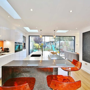 This is an example of a medium sized contemporary single-wall kitchen in London with a submerged sink, flat-panel cabinets, white cabinets, orange splashback, light hardwood flooring, an island and beige floors.
