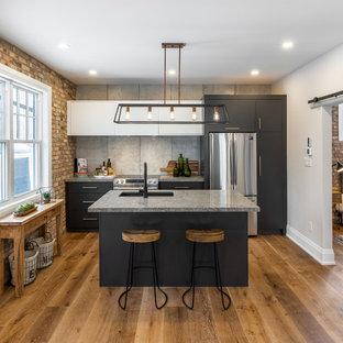 Inspiration för ett litet industriellt grå grått parallellkök, med en undermonterad diskho, släta luckor, bänkskiva i kvarts, grått stänkskydd, rostfria vitvaror, mellanmörkt trägolv, en köksö, brunt golv och svarta skåp