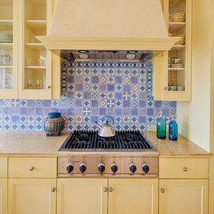 Diseño de cocina mediterránea con armarios tipo vitrina, puertas de armario amarillas, encimera de granito, electrodomésticos de acero inoxidable, suelo de madera clara y salpicadero azul