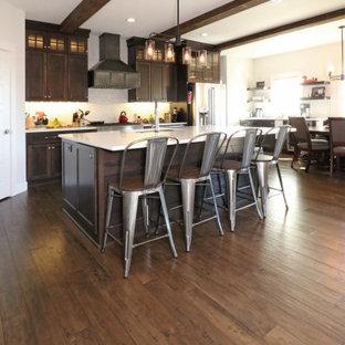 他の地域のインダストリアルスタイルのおしゃれなキッチン (エプロンフロントシンク、シェーカースタイル扉のキャビネット、濃色木目調キャビネット、珪岩カウンター、白いキッチンパネル、シルバーの調理設備の、無垢フローリング、茶色い床、白いキッチンカウンター) の写真