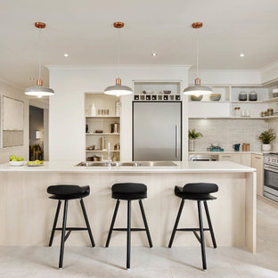 Photo of a contemporary l-shaped kitchen in Melbourne with a double-bowl sink, flat-panel cabinets, light wood cabinets, beige splashback, matchstick tile splashback, stainless steel appliances and with island.