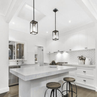 Inspiration for a small victorian galley open plan kitchen in Melbourne with an undermount sink, shaker cabinets, white cabinets, quartz benchtops, white splashback, subway tile splashback, stainless steel appliances, medium hardwood floors, with island, brown floor and grey benchtop.