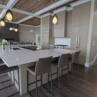 Expansive modern u-shaped open plan kitchen in Seattle with an undermount sink, flat-panel cabinets, beige cabinets, wood benchtops, white splashback, panelled appliances, bamboo floors and with island.
