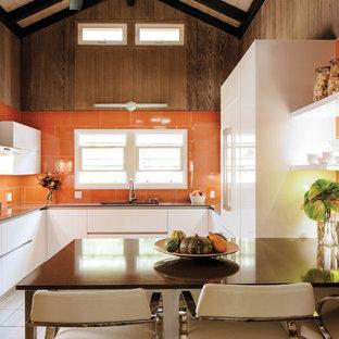 ハワイの中くらいのコンテンポラリースタイルのおしゃれなキッチン (フラットパネル扉のキャビネット、白いキャビネット、クオーツストーンカウンター、オレンジのキッチンパネル、セラミックタイルのキッチンパネル、シングルシンク) の写真