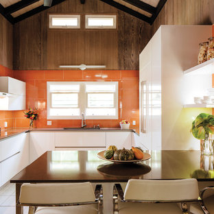 Mid-sized contemporary u-shaped separate kitchen in Hawaii with flat-panel cabinets, white cabinets, quartz benchtops, orange splashback, ceramic splashback, a peninsula and a single-bowl sink.