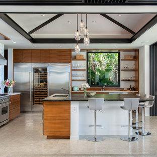 他の地域のトロピカルスタイルのおしゃれなキッチン (アンダーカウンターシンク、フラットパネル扉のキャビネット、中間色木目調キャビネット、シルバーの調理設備の、グレーの床、白いキッチンカウンター) の写真
