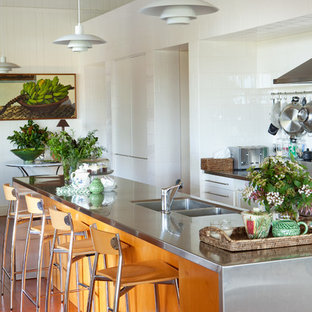 Large contemporary galley kitchen in Brisbane with a double-bowl sink, white cabinets, stainless steel benchtops, white splashback, ceramic splashback, stainless steel appliances, medium hardwood floors and with island.