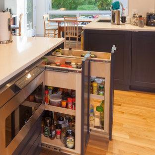 Geschlossene, Große Klassische Küche mit Doppelwaschbecken, Schrankfronten im Shaker-Stil, grauen Schränken, Quarzwerkstein-Arbeitsplatte, Küchenrückwand in Grau, Glasrückwand, hellem Holzboden und Kücheninsel in Seattle