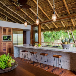 This is an example of a tropical open plan kitchen in Hawaii with louvered cabinets, medium wood cabinets, medium hardwood floors and with island.