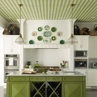 На фото: кухня в классическом стиле с врезной раковиной, фасадами с выступающей филенкой, зелеными фасадами, белым фартуком и техникой из нержавеющей стали с