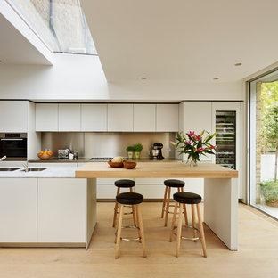 ロンドンの北欧スタイルのおしゃれなアイランドキッチン (フラットパネル扉のキャビネット、白いキャビネット、淡色無垢フローリング、パネルと同色の調理設備) の写真