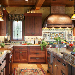 This is an example of a large country u-shaped eat-in kitchen in New York with recessed-panel cabinets, distressed cabinets, concrete benchtops, medium hardwood floors, an integrated sink and panelled appliances.