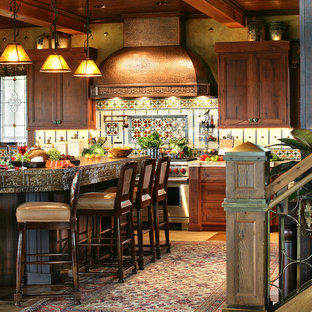 Large mountain style u-shaped medium tone wood floor kitchen photo in New York with recessed-panel cabinets, dark wood cabinets, concrete countertops, multicolored backsplash and stainless steel appliances
