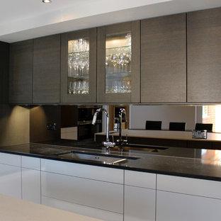 ロンドンの広いモダンスタイルのおしゃれなキッチン (フラットパネル扉のキャビネット、グレーのキャビネット、珪岩カウンター、メタリックのキッチンパネル、アンダーカウンターシンク、ミラータイルのキッチンパネル、黒い調理設備、磁器タイルの床) の写真