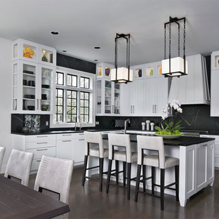 Large contemporary l-shaped eat-in kitchen in Detroit with a drop-in sink, shaker cabinets, white cabinets, soapstone benchtops, black splashback, stone slab splashback, stainless steel appliances, dark hardwood floors, with island and brown floor.