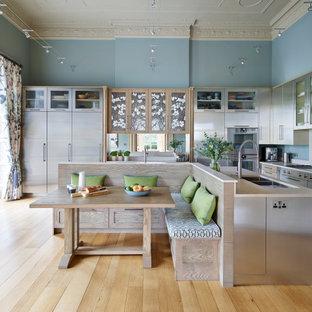 Geschlossene, Große Moderne Küche mit Einbauwaschbecken, flächenbündigen Schrankfronten, Edelstahlfronten, Quarzit-Arbeitsplatte, Küchenrückwand in Beige, Küchengeräten aus Edelstahl, hellem Holzboden, Kücheninsel und beiger Arbeitsplatte in Berkshire