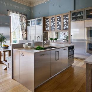 バークシャーの広いコンテンポラリースタイルのおしゃれなキッチン (ドロップインシンク、フラットパネル扉のキャビネット、ステンレスキャビネット、珪岩カウンター、ベージュキッチンパネル、シルバーの調理設備、淡色無垢フローリング、ベージュのキッチンカウンター) の写真