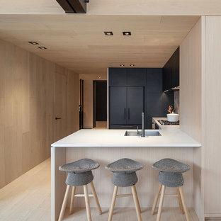 Ejemplo de cocina en U, minimalista, de tamaño medio, con fregadero bajoencimera, armarios con paneles lisos, puertas de armario negras, electrodomésticos negros y península