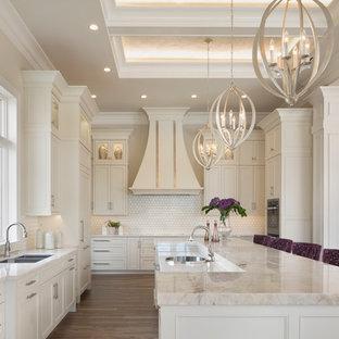 Bild på ett avskilt, stort funkis beige beige l-kök, med en undermonterad diskho, luckor med infälld panel, vitt stänkskydd, rostfria vitvaror, mörkt trägolv, en köksö, brunt golv, beige skåp, bänkskiva i kvartsit och stänkskydd i porslinskakel