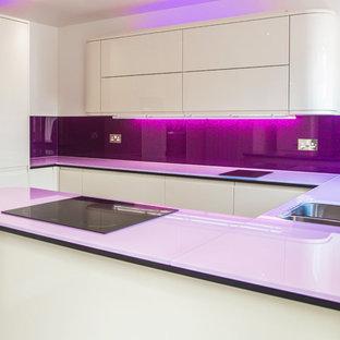 ロンドンの広いコンテンポラリースタイルのおしゃれなキッチン (ガラスカウンター、ガラス板のキッチンパネル、アンダーカウンターシンク、フラットパネル扉のキャビネット、白いキャビネット、メタリックのキッチンパネル、シルバーの調理設備) の写真
