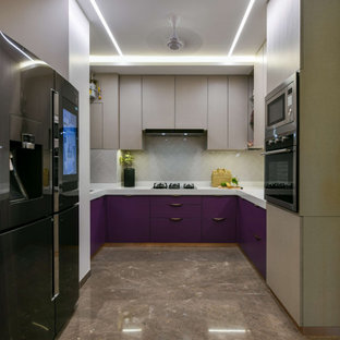 This is an example of a mid-sized contemporary u-shaped kitchen in Mumbai with flat-panel cabinets, purple cabinets, grey splashback, black appliances, no island, brown floor and white benchtop.