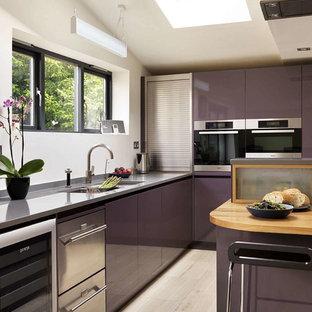 Exempel på ett modernt kök med öppen planlösning, med släta luckor, lila skåp, bänkskiva i koppar, rostfria vitvaror och en halv köksö