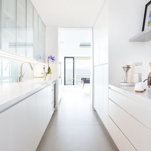 Contemporary galley kitchen in Salt Lake City with flat-panel cabinets, white cabinets, glass sheet splashback, no island and grey floors.
