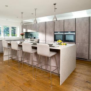 Design ideas for a contemporary kitchen/diner in Essex with flat-panel cabinets, grey cabinets, engineered stone countertops, grey splashback, mirror splashback, black appliances, medium hardwood flooring, an island, brown floors and white worktops.