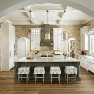 Идея дизайна: огромная п-образная кухня-гостиная в средиземноморском стиле с белыми фасадами, столешницей из кварцита, фартуком из кирпича, паркетным полом среднего тона, островом, фасадами с утопленной филенкой, раковиной в стиле кантри, серым фартуком, техникой под мебельный фасад, коричневым полом, белой столешницей и кессонным потолком