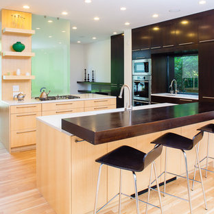 Photo of a medium sized contemporary u-shaped open plan kitchen in DC Metro with flat-panel cabinets, dark wood cabinets, wood worktops, stainless steel appliances, a submerged sink, light hardwood flooring, multiple islands, beige floors and white worktops.